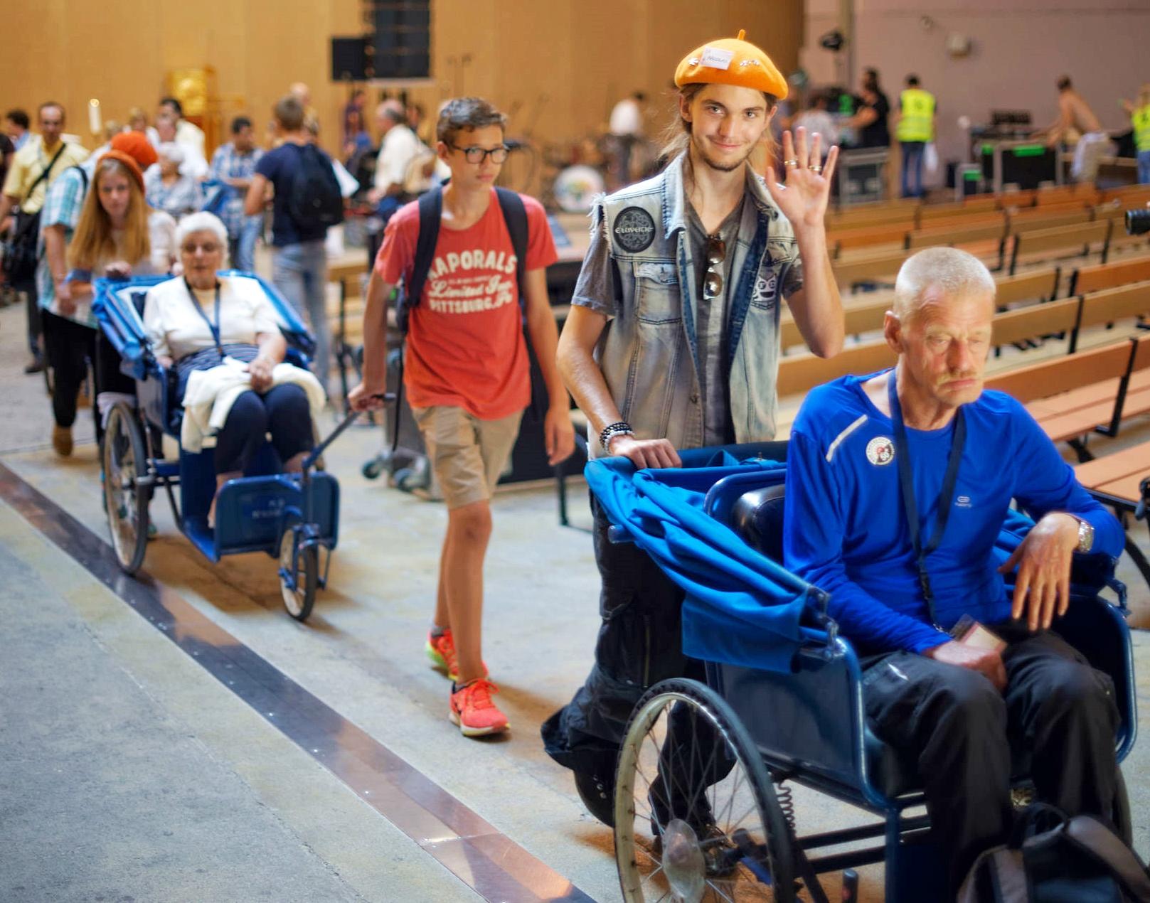 Des jeunes OH accompagnent des malades lors de la messe d'ouverture.